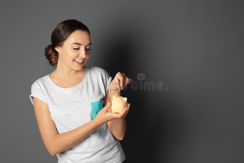 Jeune femme mettant la pièce de monnaie dans la tirelire photographie stock