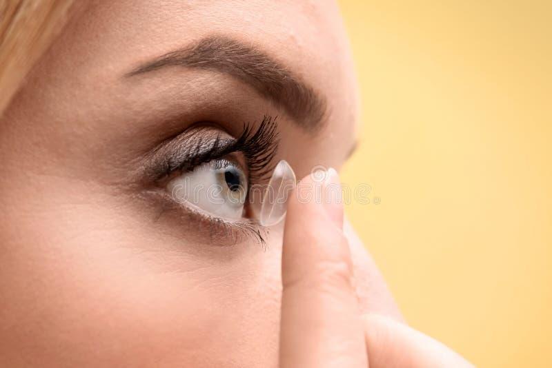 Jeune femme mettant le verre de contact dans son oeil photo stock