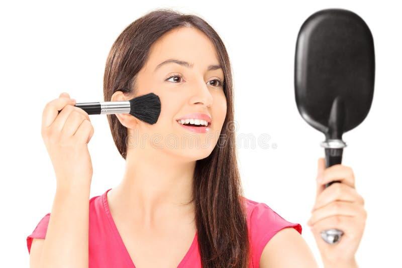 Jeune femme mettant sur le maquillage images stock