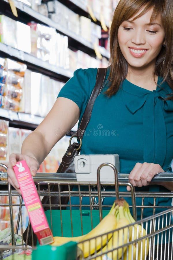 Jeune femme mettant un paquet dans un chariot à achats photographie stock