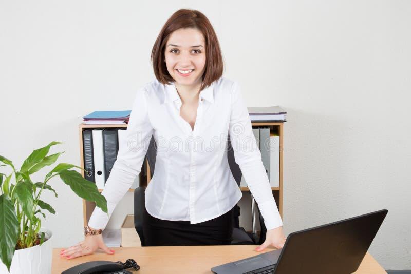 Jeune femme mignonne à l'aide de l'ordinateur portable tout en se tenant à son bureau photo stock