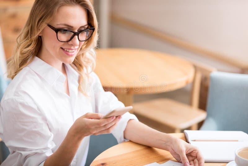 Jeune femme mignonne à l'aide du téléphone photo stock