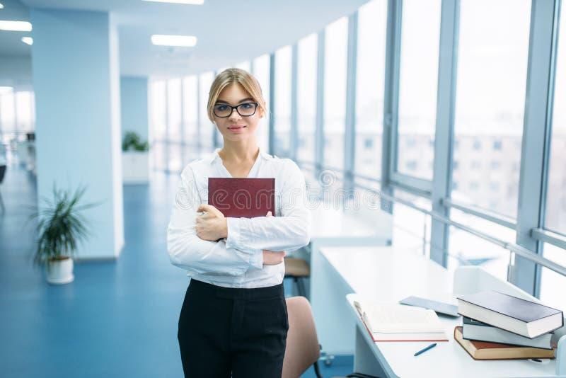 Jeune femme mignonne avec le livre dans la bibliothèque photo libre de droits
