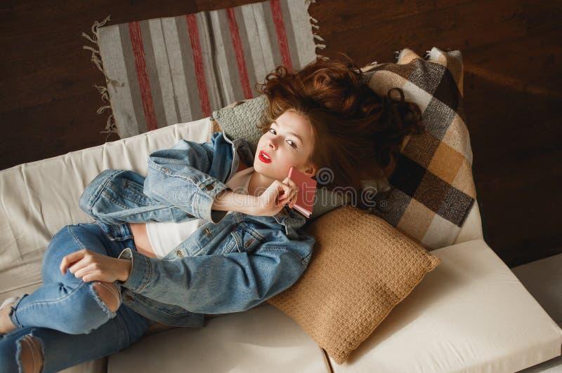 Jeune femme mignonne dans des vêtements de jeans se situant dans le sofa avec le journal intime rose photos stock