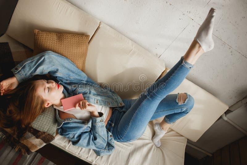 Jeune femme mignonne dans des vêtements de jeans se situant dans le sofa avec le journal intime rose image stock