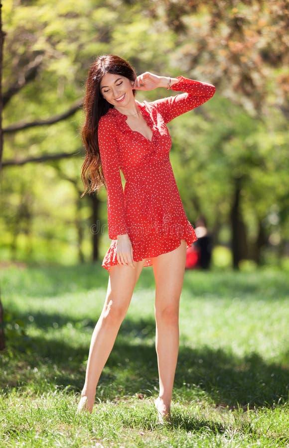 Jeune femme mignonne dans la danse rouge de robe nu-pieds en parc Sc?ne de nature de beaut? avec le fond color?, arbres ? la sais image stock