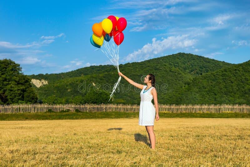 Jeune femme mignonne dans la robe blanche avec des ballons dans des ses mains Le concept de la liberté et de la joie photo stock
