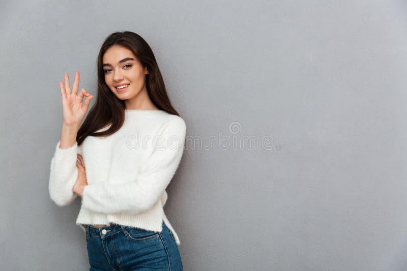 Jeune femme mignonne de brune dans le chandail pelucheux blanc montrant les ges CORRECTS photographie stock libre de droits
