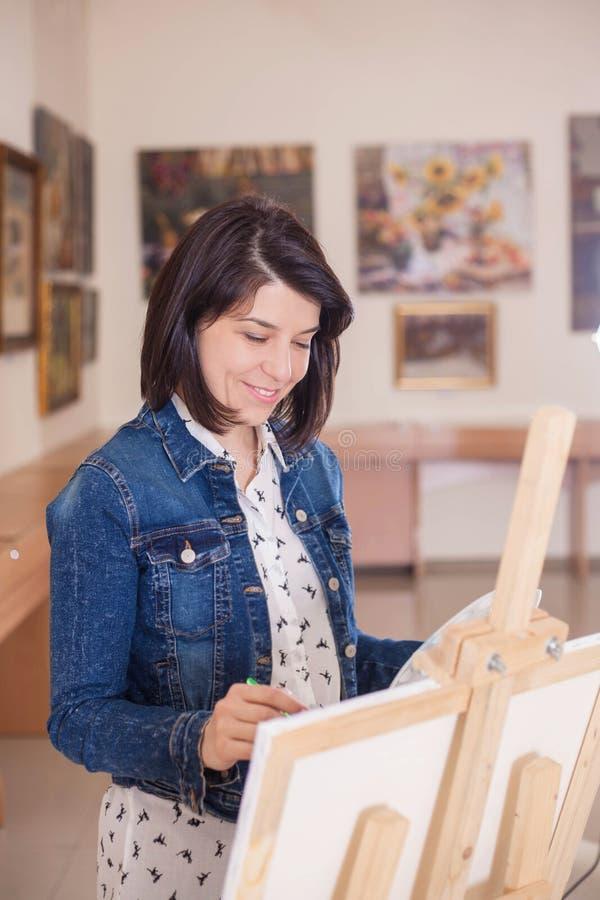 Jeune femme mignonne peignant un tableau près d'un chevalet dans un studio photos stock