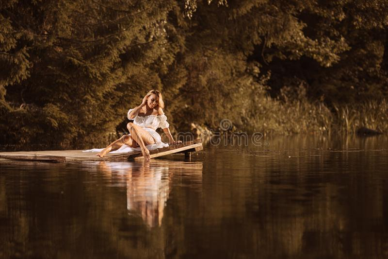 Jeune femme mignonne s'asseyant par le lac touchant l'eau par sa jambe image stock