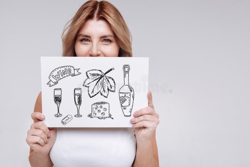 Jeune femme mignonne souriant et pensant au vin potable images stock