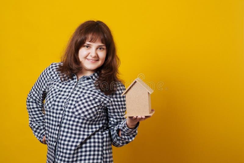 Jeune femme mignonne tenant un modèle de maison sur le fond jaune image libre de droits