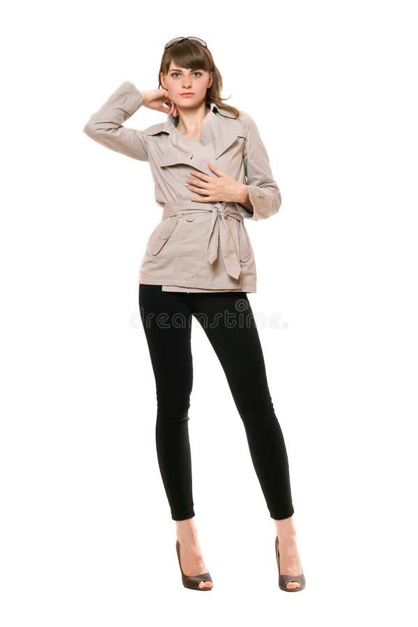 Jeune femme mignonne utilisant un manteau et des guêtres noires image stock