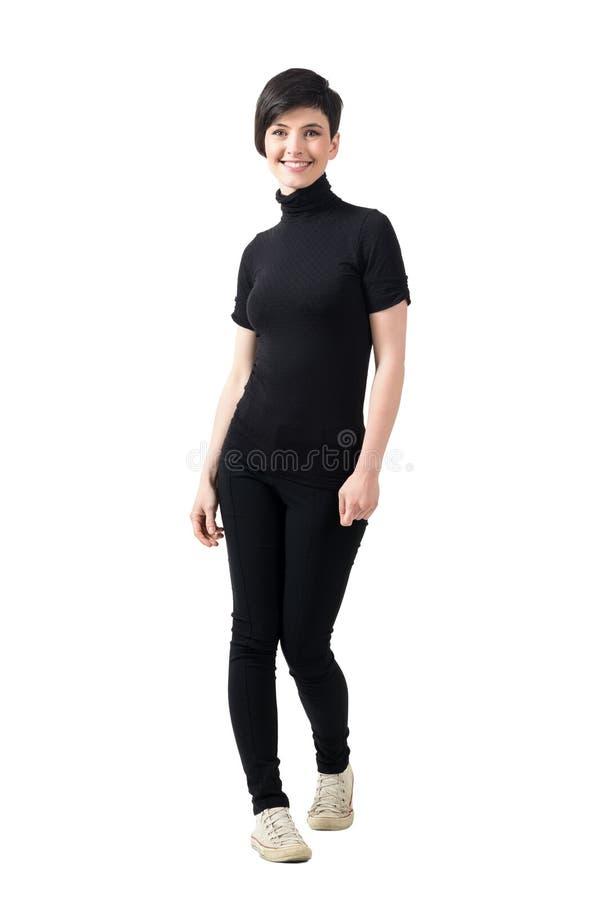 Jeune femme mince à la mode de cheveux courts dans le T-shirt et le pantalon noirs de col roulé souriant à l'appareil-photo photographie stock libre de droits