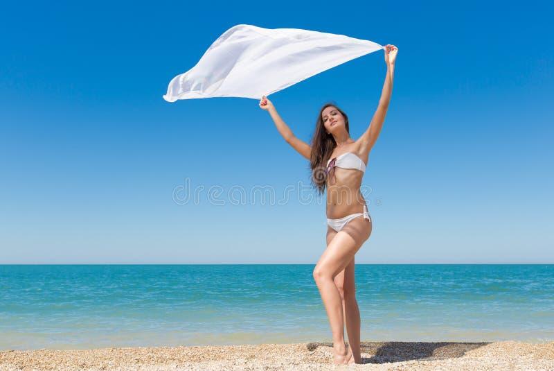 Jeune femme mince avec le pareo posant sur le bord de la mer images libres de droits