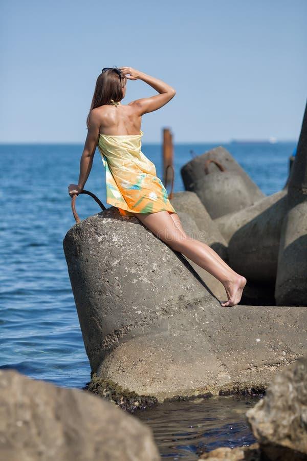 Jeune femme mince dans le pareo sur le brise-lames photo stock