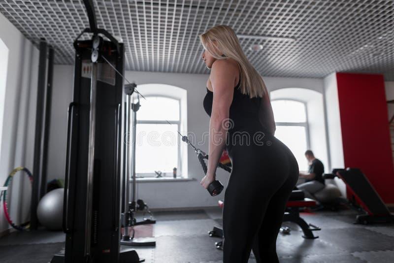 Jeune femme mince dans les vêtements de sport à la mode faisant des exercices de force pour des mains dans un gymnase moderne fil photo stock