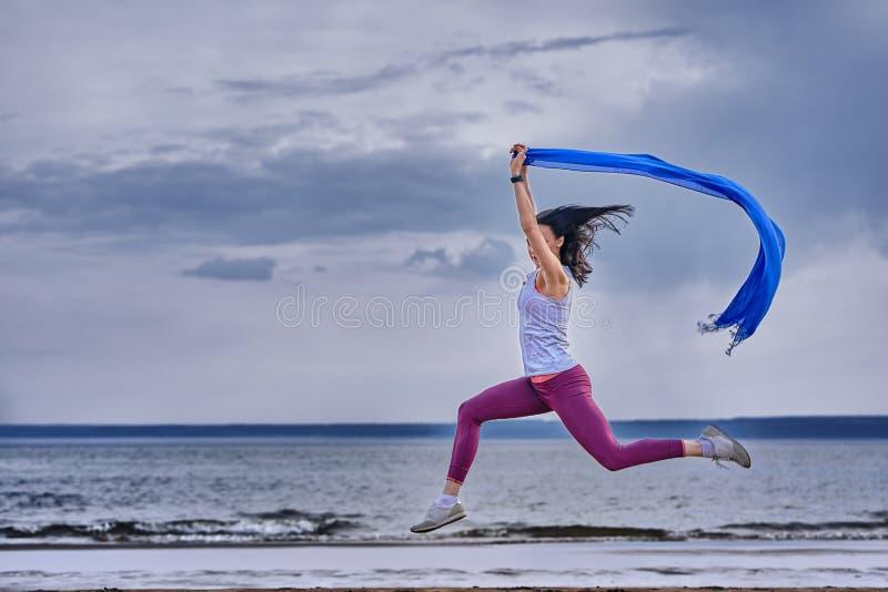 Jeune femme mince de brune sautant tout en pulsant tout en tenant une écharpe bleue dans des ses mains Une femme est engagée en g photographie stock
