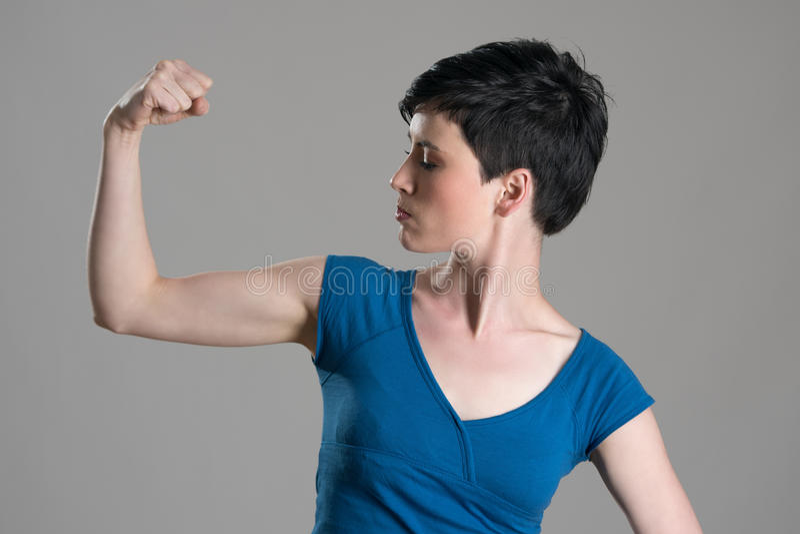 Jeune femme mince de cheveux courts fléchissant le muscle de biceps de bras photographie stock
