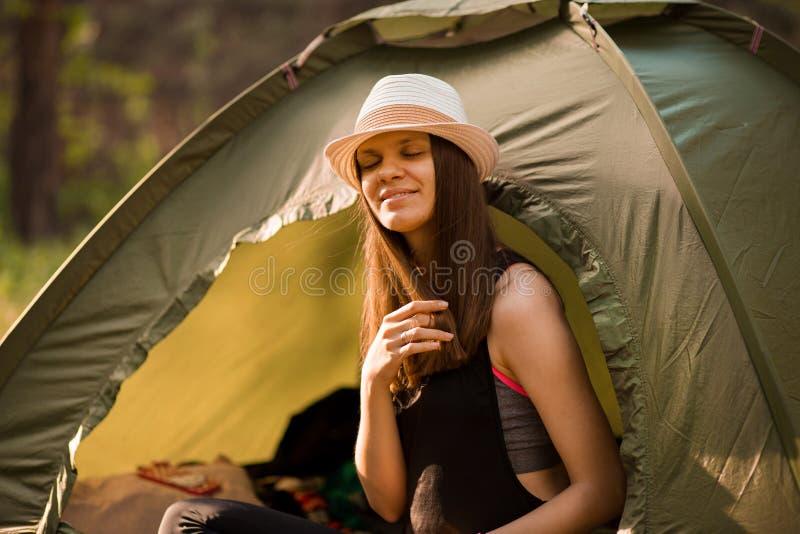 Jeune femme mince de randonneur s'asseyant ? la petite tente de touristes appr?ciant la belle for?t de nature le matin lumineux d image stock