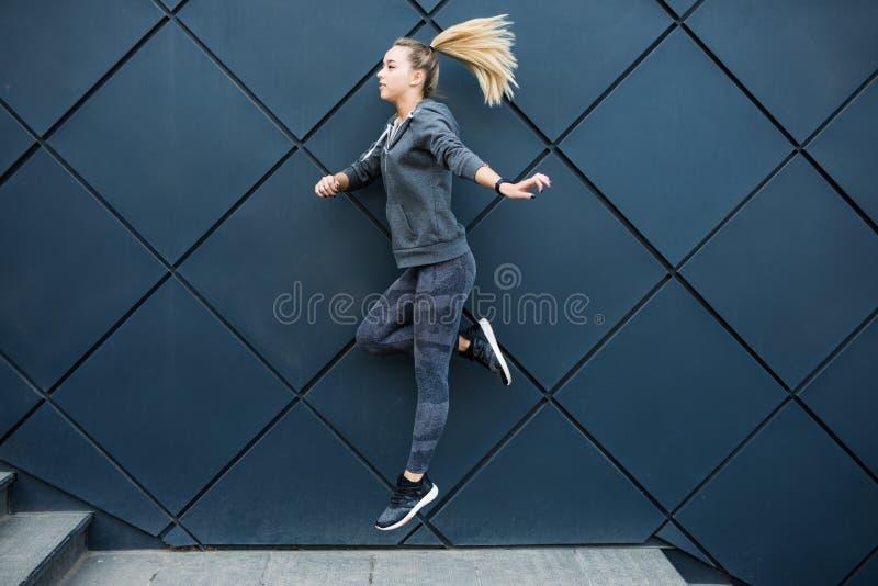 Jeune femme mince de sports dans l'habillement de forme physique sautant sur le fond noir de mur dehors images stock