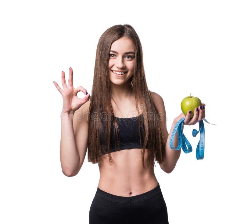 Jeune femme mince et en bonne santé tenant la bande de mesure et pomme d'isolement sur le fond blanc Perte de poids et concept de photos libres de droits