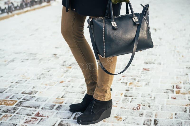 Jeune femme mince marchant en parc avec la bourse dans le winte image stock