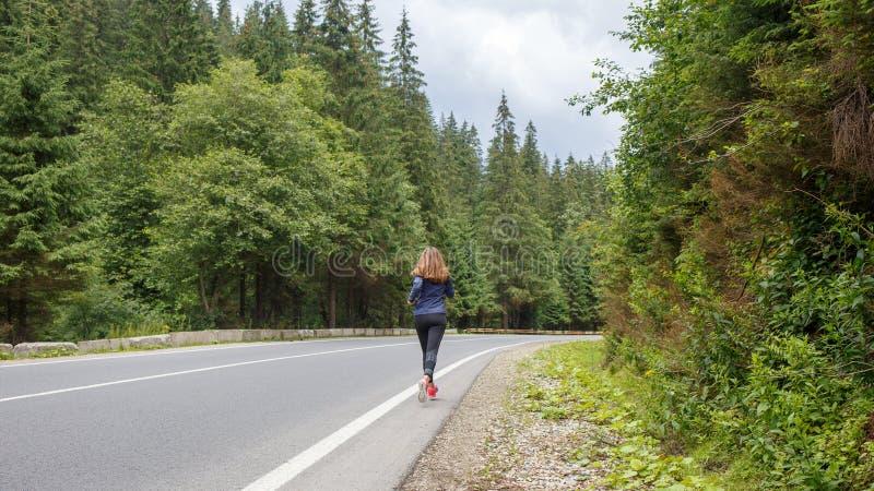 Jeune femme mince pulsant en montagnes blanc d'isolement de vue arri?re images stock