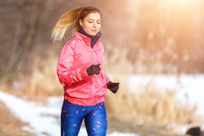 Jeune femme mince pulsant en parc d'hiver photo stock