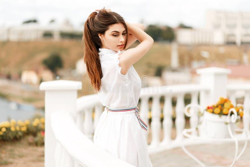 Jeune femme modèle à la mode dans la pose blanche de robe photos libres de droits