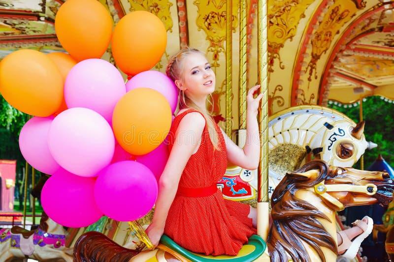 Jeune femme modèle montant un carrousel images stock