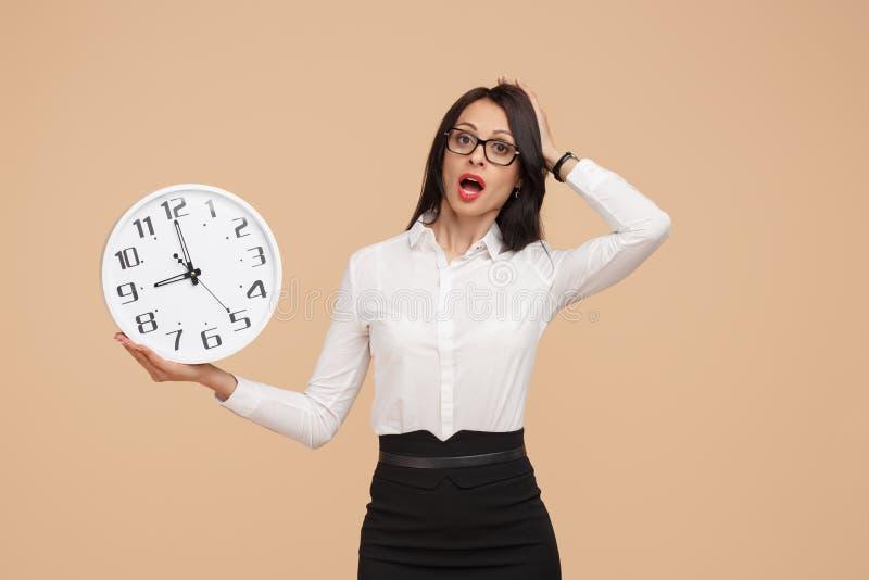 Jeune femme moderne choquée d'affaires tenant une horloge au-dessus de fond beige photos stock