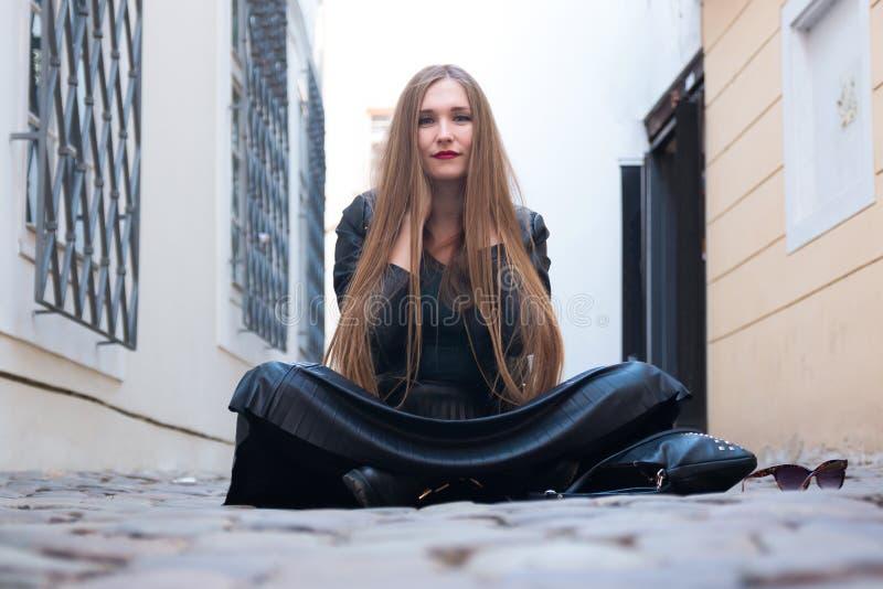 Jeune femme moderne s'asseyant dans la rue images stock