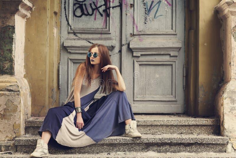 Jeune femme moderne s'asseyant sur les escaliers dans la longue robe images stock