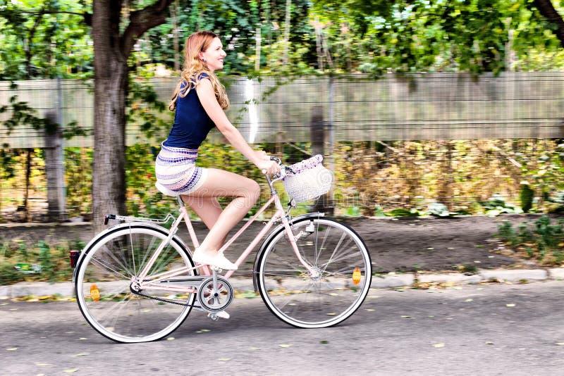 Jeune femme montant une bicyclette photos stock