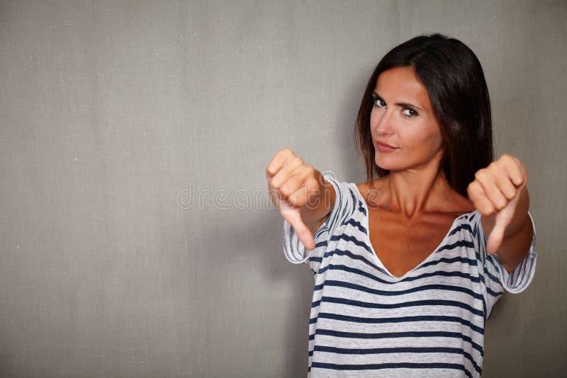 Jeune femme montrant le signe de désapprobation à l'appareil-photo photographie stock libre de droits