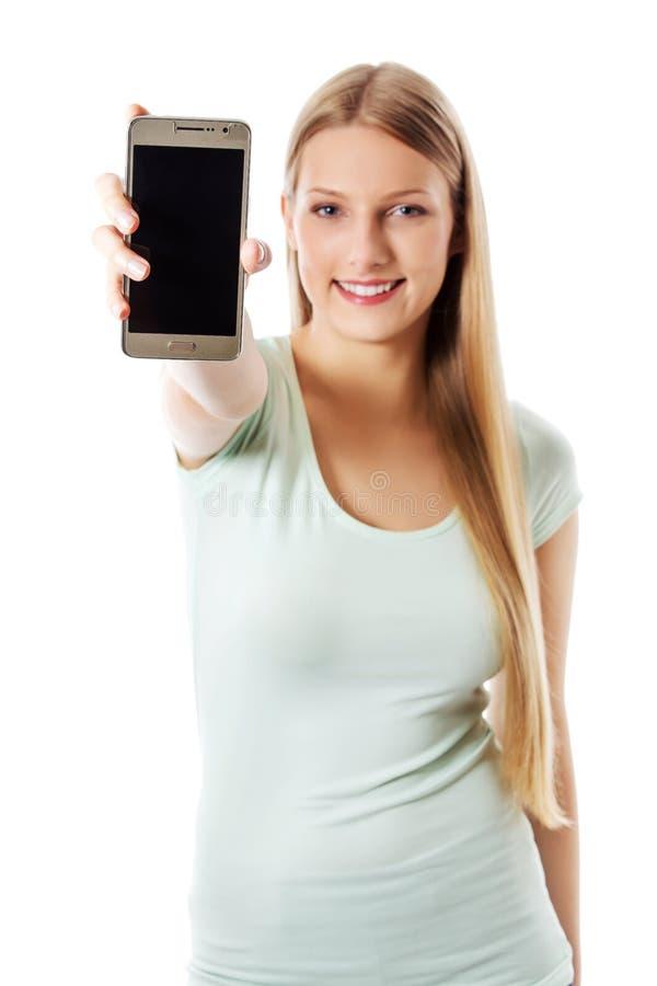 Jeune femme montrant le téléphone portable mobile avec l'écran noir photos libres de droits