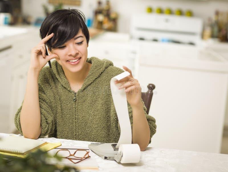 Jeune femme multi-ethnique souriant au-dessus des calculs financiers photos stock