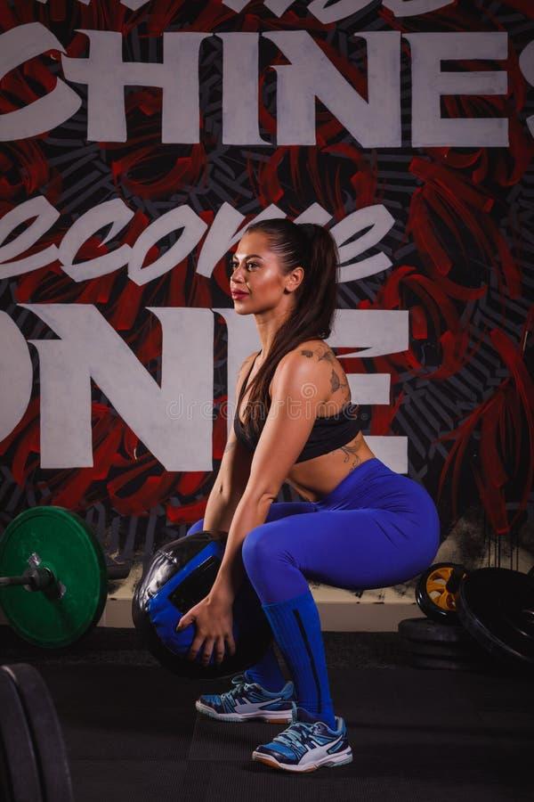 Jeune femme musculaire attirante établissant avec des boules dans le gymnase photographie stock libre de droits