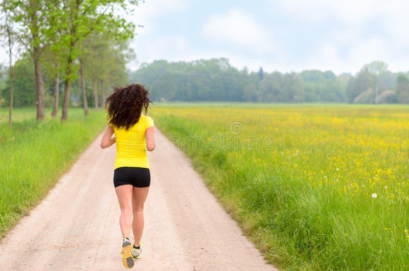 Jeune femme musculaire convenable pulsant dans les terres cultivables image stock