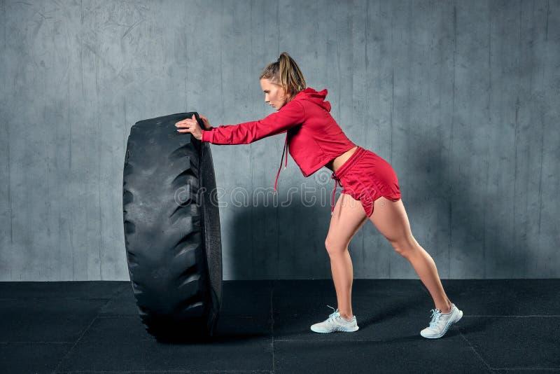 Jeune femme musculaire renversant un pneu sur la formation dure avec l'entraîneur personnel au gymnase de garage photos stock