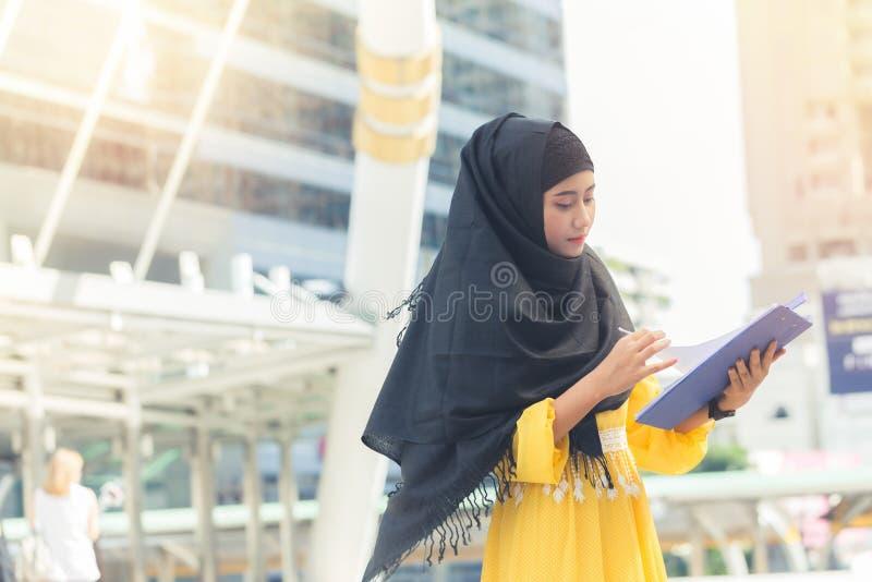 Jeune femme musulmane asiatique d'affaires souriant et position de fichier de recopie document et à la capitale photographie stock libre de droits