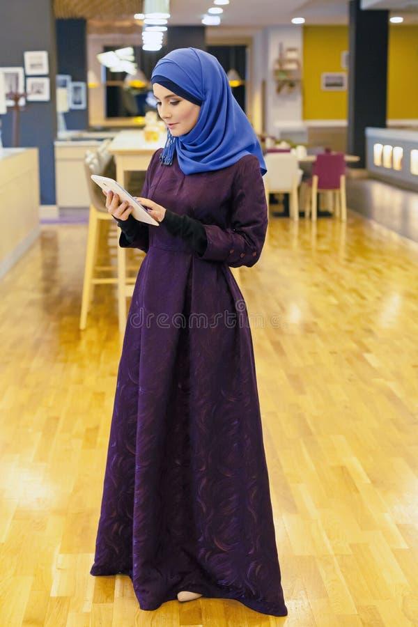 Jeune femme musulmane avec un comprimé électronique dans des ses mains photographie stock libre de droits
