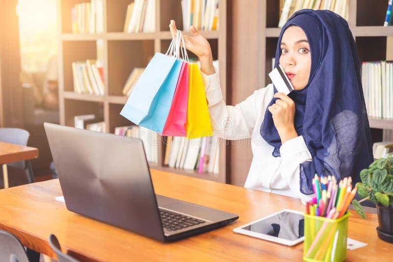 Jeune femme musulmane montrant une carte de crédit et coloré heureux photographie stock