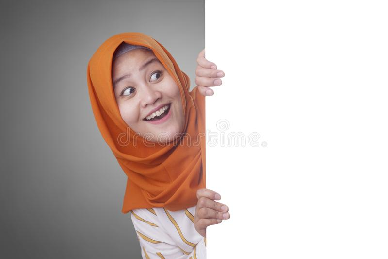 Jeune femme musulmane souriant derri?re le conseil blanc vide image stock