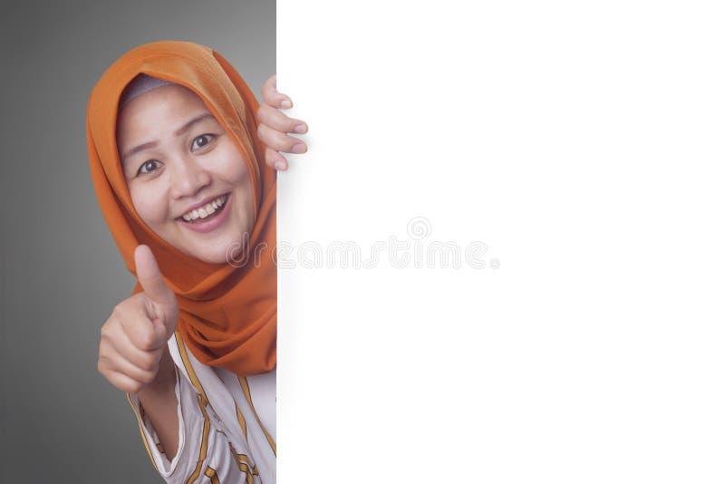 Jeune femme musulmane souriant derri?re le conseil blanc vide photos stock