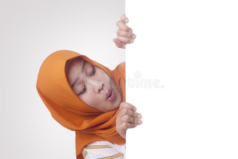 Jeune femme musulmane souriant derri?re le conseil blanc vide photos libres de droits