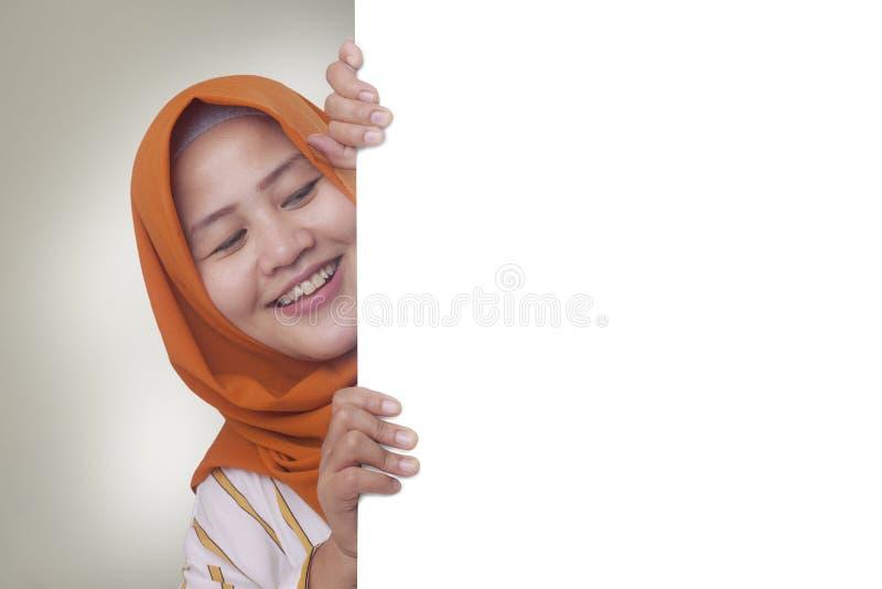 Jeune femme musulmane souriant derri?re le conseil blanc vide photographie stock libre de droits