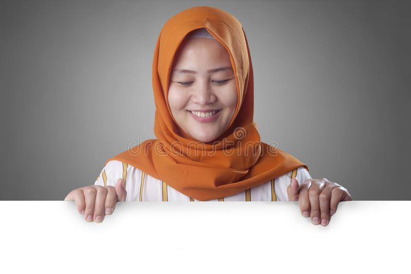 Jeune femme musulmane souriant derri?re le conseil blanc vide photo stock