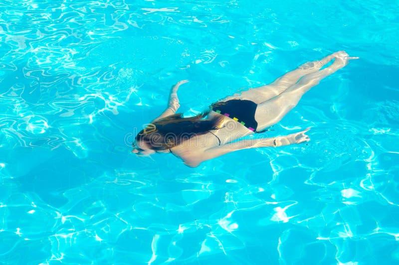 Jeune femme nageant sous l'eau dans le regroupement photos stock